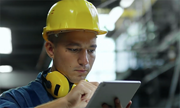 Worker in hardhat working on tablet
